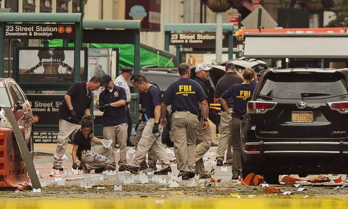 Members of the Federal Bureau of Investigation (FBI) carry on investigations at the scene of Saturday's explosion on West 23rd Street and Sixth Avenue in Manhattan's Chelsea neighborhood, in New York, on Sunday, Sept. 18, 2016. (AP Photo/Andres Kudacki)