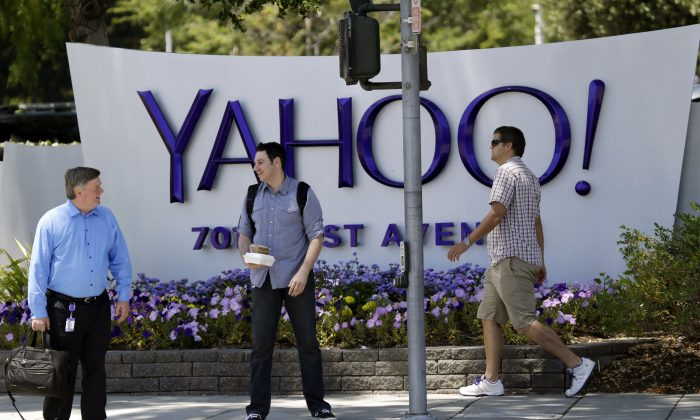 People walk in front of a Yahoo sign at the company's headquarters in Sunnyvale, CA., in this file photo. (AP Photo/Marcio Jose Sanchez)