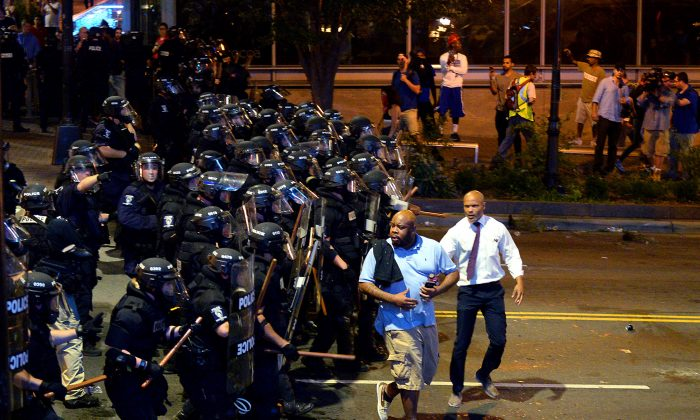 Charlotte-Mecklenburg police officers begin to push protesters from the intersection near the Epicentre in Charlotte, N.C., on Sept. 21, 2016. (Jeff Siner/The Charlotte Observer via AP)