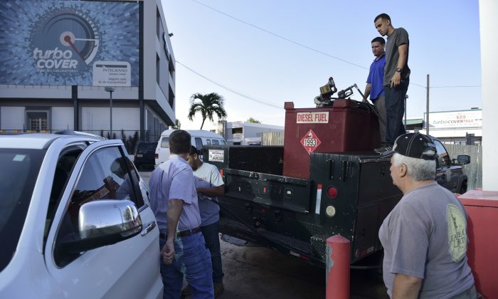 Department of Education employees fill a generator with diesel in San Juan, Puerto Rico on Sept. 22, 2016. (AP Photo/Carlos Giusti)