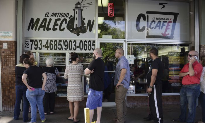 Customers stand in line at one of the few open cafeterias on Roosevelt Avenue, in San Juan, Puerto Rico on Sept. 22, 2016, (AP Photo/Carlos Giusti)