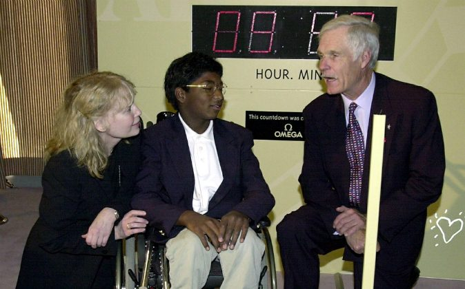 US Actress Mia Farrow (L) and her adopted son Thaddeus, whos suffers from polio (C), talk with media mogul Ted Turner (R) before a United Nations conference on the eradication of polio in New York, New York 27 September, 2000. Thaddeus died from injuries sustained from a car accident on Sept. 21. (HENNY RAY ABRAMS/AFP/Getty Images)
