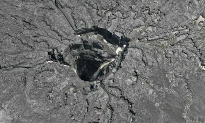 This aerial photo shows a massive sinkhole Friday, Sept. 16, 2016, in Mulberry, Fla., that opened up underneath a gypsum stack at a Mosaic phosphate fertilizer plant. Tens of millions of gallons of reprocessed water from the fertilizer plant in central Florida are likely to have seeped into the Floridan aquifer after the massive sinkhole opened up. Mosaic says it's monitoring groundwater and has found no offsite impact. (Jim Damaske/Tampa Bay Times via AP)