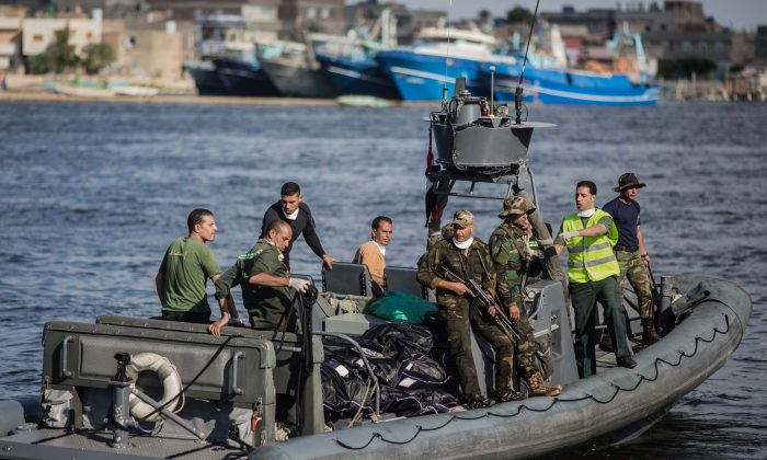 An Egyptian coast guard dinghy brings bodies from a Europe-bound boat that capsized off Egypt's Mediterranean coast, to the shore in Rosetta, Egypt on Sept. 22, 2016. (AP Photo/Eman Helal)