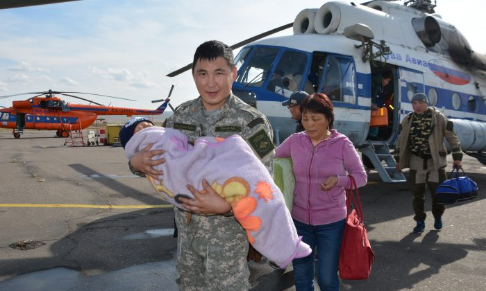 An unidentified special force soldier carries a 3-year old boy rescued after going missing for three days in an undisclosed location in the Russian Siberian region of Tuva. (Tuva Emergency Situations Ministry press service photo via AP)