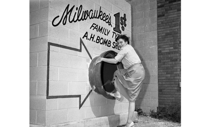 A woman shows how to enter a family bomb shelter in Milwaukee in 1958. (AP Photo)