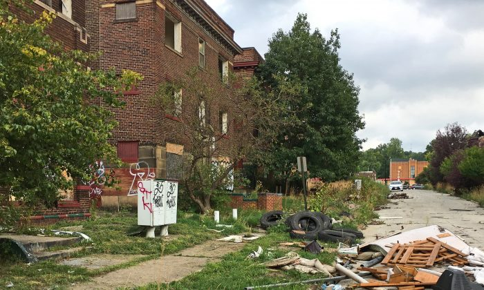 Discarded tires and other refuse pile up on cracked pavement and sidewalks alongside graffiti-scarred buildings with missing windows in East Cleveland, Ohio, on Aug. 31, 2016. Cleveland and East Cleveland, two of the country's poorest cities, are debating whether to merge, with both cities saying the state of Ohio needs to provide millions to begin fixing East Cleveland's infrastructure and finances. (AP Photo/Mark Gillispie)
