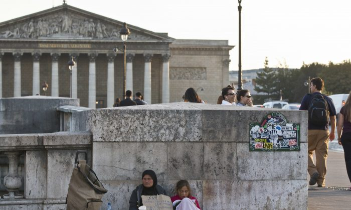 A migrant family beg for money at the Concorde bridge next to the French parliament in Paris on Sept.21, 2016. (AP Photo/Michel Euler)