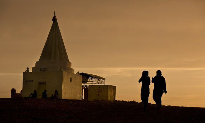 The sun sets as women visit a Yazidi shrine overlooking at Kankhe Camp for the internally displaced in Dahuk, northern Iraq, on May 18, 2016. (AP Photo/Maya Alleruzzo)
