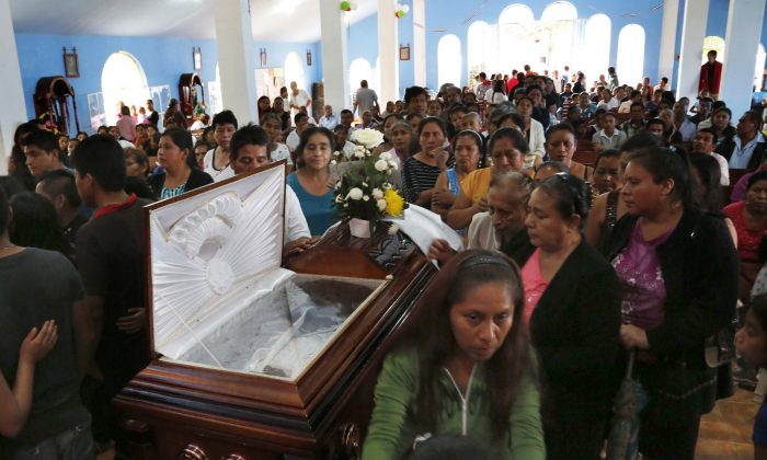 People paying their last respects on Sept. 21, 2016 to slain Rev. Jose Alfredo Suarez de la Cruz, who was found bound and shot to death alongside another priest, inside Our Lady of Asuncion Church in Paso Blanco, Veracruz state, Mexico, his hometown. In this eastern oil town already weary of rising gangland violence and extortion, the abduction and murder of two priests this week sank many residents only deeper into despair. (AP Photo/Marco Ugarte)