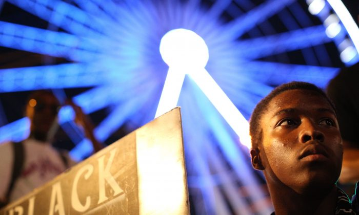 A demonstrator holds a sign during a protest in Atlanta on Friday, Sept. 23, 2016 in response to the police shooting deaths of Terence Crutch in Tulsa, Okla. and Keith Lamont Scott in Charlotte, N.C. (AP Photo/Branden Camp)