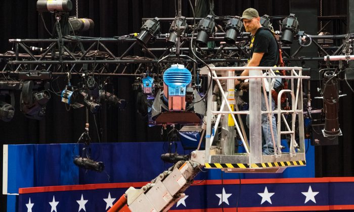 A technician examines the lighting grid as preparations continue for Monday's first debate presidential between Democratic Hillary Clinton and Republican Donald Trump at Hofstra University in Hempstead, N.Y., on Sept. 24, 2016. (AP Photo/J. David Ake)