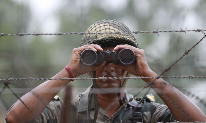 An Indian Border Security Force soldier looks at the Pakistan side of the border through a binocular at Ranbir Singh Pura, about 35 kilometers (22 miles) from Jammu, India, on Sept. 24, 2016. (AP Photo/Channi Anand)