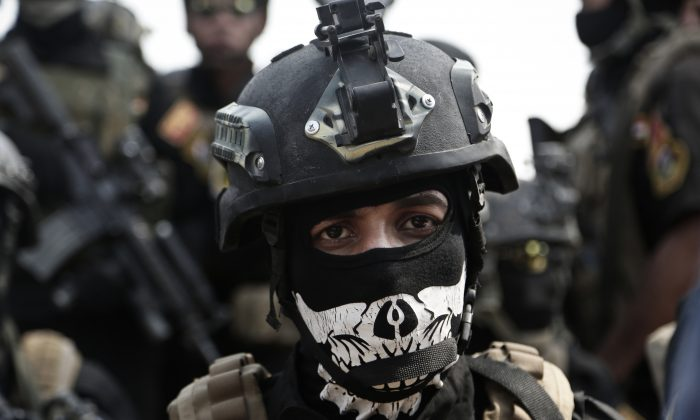 A soldier from the 1st Battalion of the Iraqi Special Operations Forces listens to an address by his commander after a training exercise to prepare for the operation to retake Mosul from Islamic State militants, in Baghdad, Iraq, on Aug. 13, 2016. (AP Photo/Maya Alleruzzo)