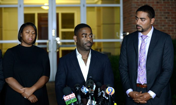 Rachel (L) and Ray Dotch (C), sister-in-law and brother-in-law to Keith Lamont Scott, give a news conference in Charlotte, N.C., on Sept. 24, 2016. (Jeff Siner/The Charlotte Observer via AP)