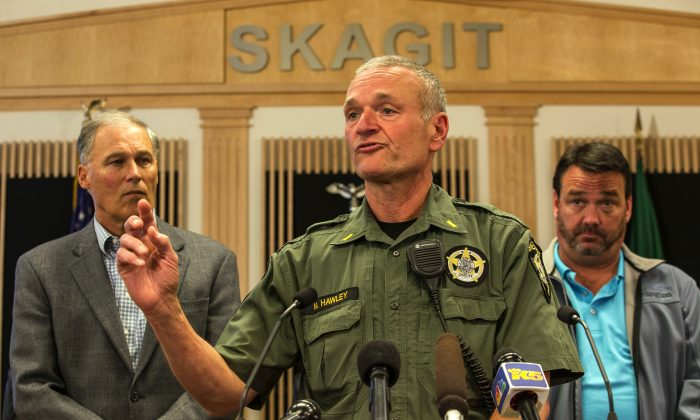 Lt. Mike Hawley with Island County Sheriff's office discusses the capture of Arcan Cetin, 20, who was wanted in connection with Friday's mass shooting at Cascade Mall in Burlington, Wash., on Friday. Officials, including Washington Gov. Jay Inslee (L), gathered in the Skagit County chambers in Mt. Vernon, Wash., on Sept. 24, 2016. (Dean Rutz/The Seattle Times via AP)