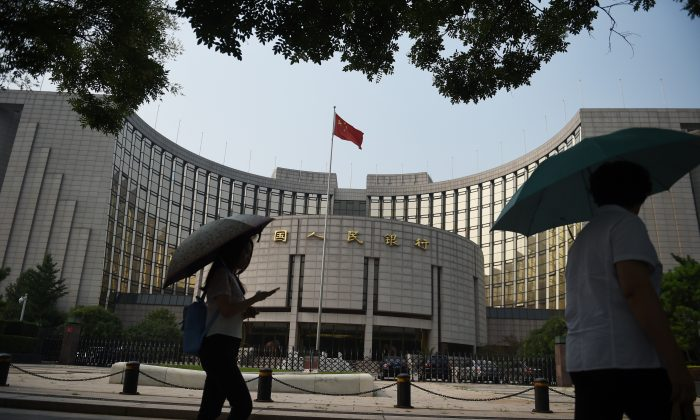 Pedestrians walk past the People's Bank of China on July 8, 2015. (Greg Baker/AFP/Getty Images)