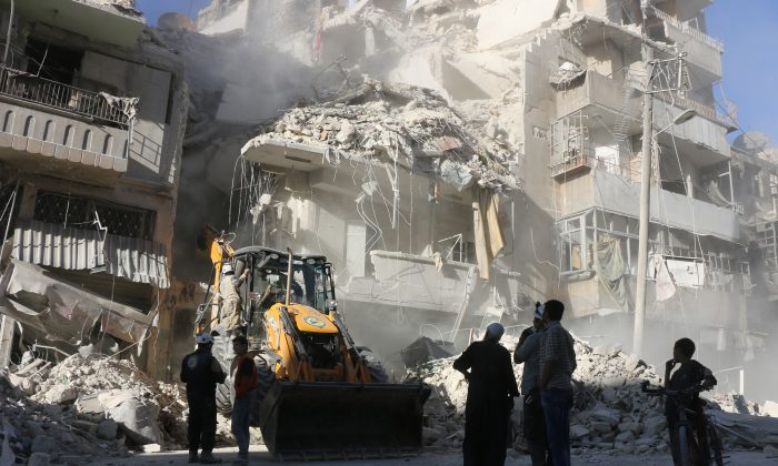 Civilians watch as a tractor clears the rubble following Syrian government forces airstrikes in the rebel held neighborhood of Tariq a-Bab in Aleppo on Sept. 24, 2016. Residents in Syria's battleground city of Aleppo cowered indoors as fierce airstrikes toppled buildings and killed at least 52 civilians, after diplomatic efforts to revive a ceasefire failed. (Thaer Mohammed/AFP/Getty Images)