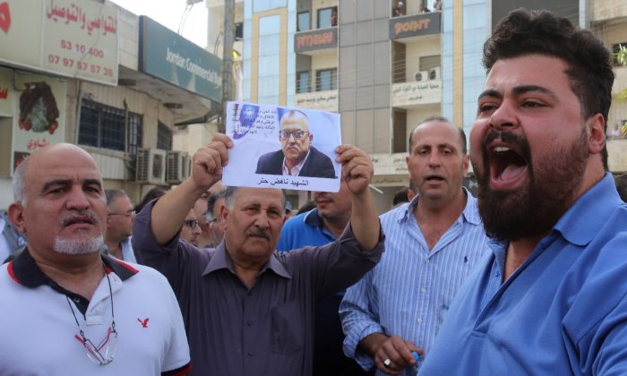 Demonstrators shout slogans during a demonstration in the town of Fuheis, 20 kilometers northwest of the capital Amman, on Sept. 25, 2016, denouncing the killing of prominent Jordanian writer Nahed Hattar (portrait). (Khalil Mazraawi/AFP/Getty Images)