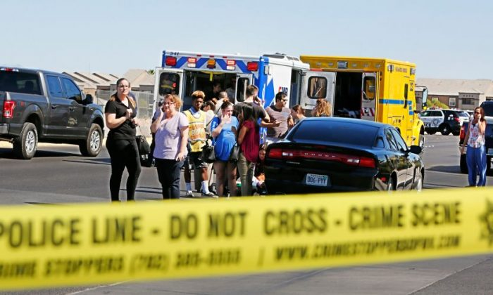 Emergency personnel stand by near Rainbow Blvd. in Las Vegas, Sunday, Sept. 25, 2016, after a shooting inside a Starbucks at a southwest valley strip mall.   (Chitose Suzuki/Las Vegas Review-Journal via AP)