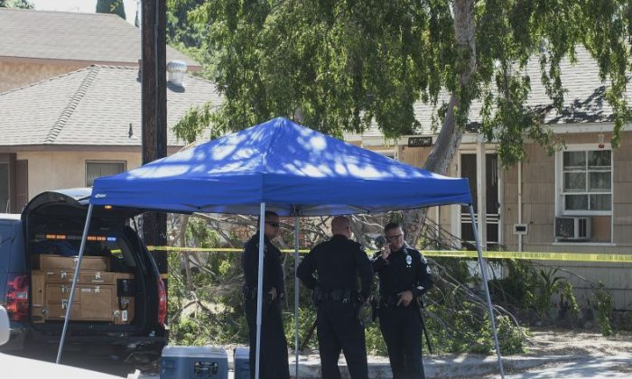 Fullerton police officers stand outside a house where three adult bodies were found in Fullerton, Calif., Saturday, Sept. 24, 2016. Police officers found two men and a woman dead in the house after a child called 911. (Nick Agro/The Orange County Register via AP)