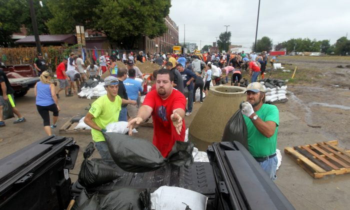 Jason Mann, of Cedar Rapids, loads sandbags onto a truck in the New Bohemia District of Cedar Rapids, Iowa, on Sept. 23, 2016. (David Scrivner /Iowa City Press-Citizen via AP)
