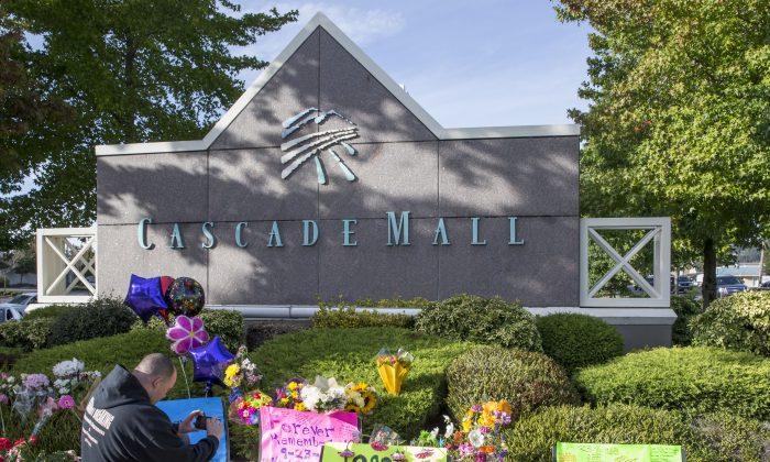 Chris Nelson of Burlington, Wash., takes a picture of a memorial in Burlington on Sept. 25, 2016. (AP Photo/Stephen Brashear)