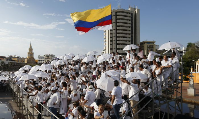 People wait for the start of the peace ceremony prior the signing of a peace agreement between Colombia's government and the Revolutionary Armed Forces of Colombia, FARC, in Cartagena, Colombia, on Sept. 26. (AP Photo/Fernando Vergara)
