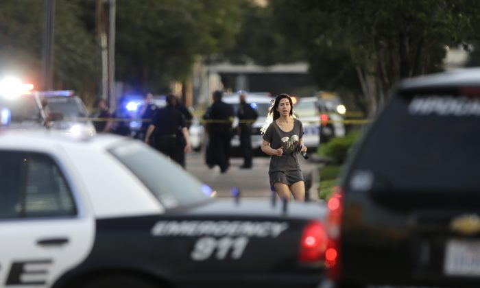 Jennifer Molleda runs down Wesleyan Street in Houston to find her husband, Alan Wakim, who had two bullets whiz by his face after going through his windshield on the way to work along Wesleyan at Law Street in a shooting that left multiple people injured and the alleged shooter dead, Monday morning, Sept. 26, 2016. (Mark Mulligan/Houston Chronicle via AP)