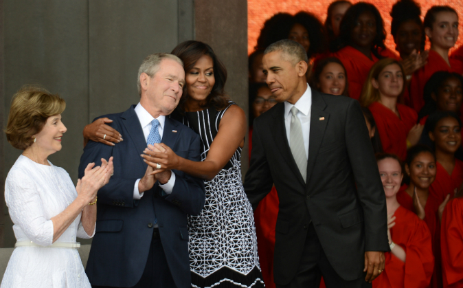 President Barack Obama watches first lady Michelle Obama embracing former president George Bush, accompanied by his wife, former first lady Laura Bush, while participating in the dedication of the National Museum of African American History and Culture September 24, 2016 in Washington, DC. (Astrid Riecken/Getty Images)