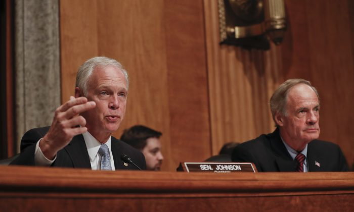 (L-R) Senate Homeland Security and Governmental Affairs Committee Chairman Sen. Ron Johnson (R-Wis.) accompanied by the committee's ranking member Sen. Tom Carper, (D-Del.) at Capitol Hill in Washington on Sept. 27, 2016.  (AP Photo/Pablo Martinez Monsivais)