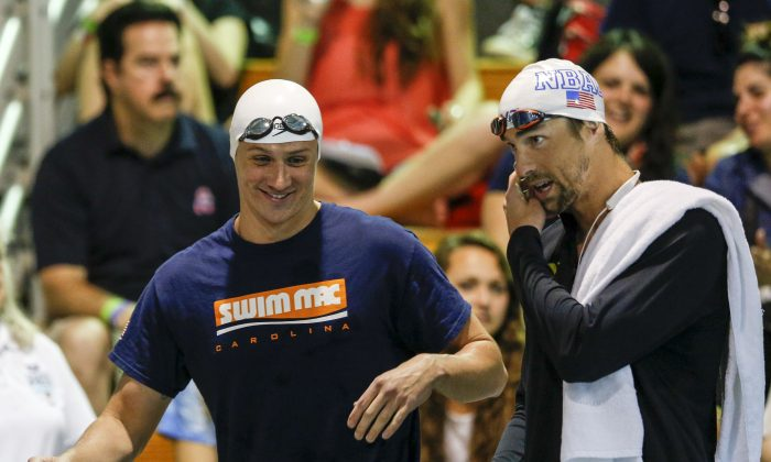 Ryan Lochte (L) and Michael Phelps talk before the start of the 100-meter butterfly final at the Arena Pro Swim Series meet in Charlotte, N.C.  (AP Photo/Nell Redmond)