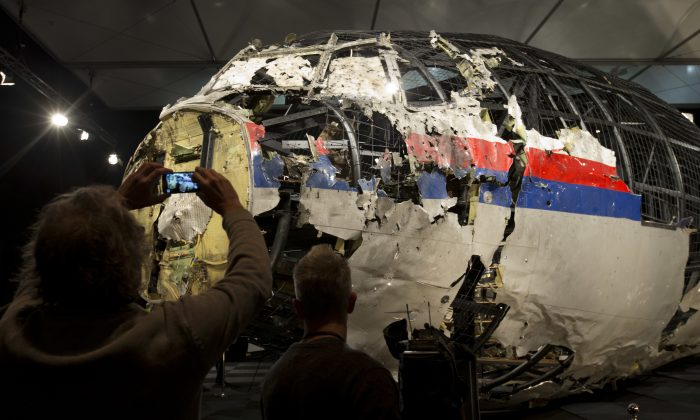 Journalists take images of part of the reconstructed forward section of the fuselage, in this file photo.  (AP Photo/Peter Dejong)