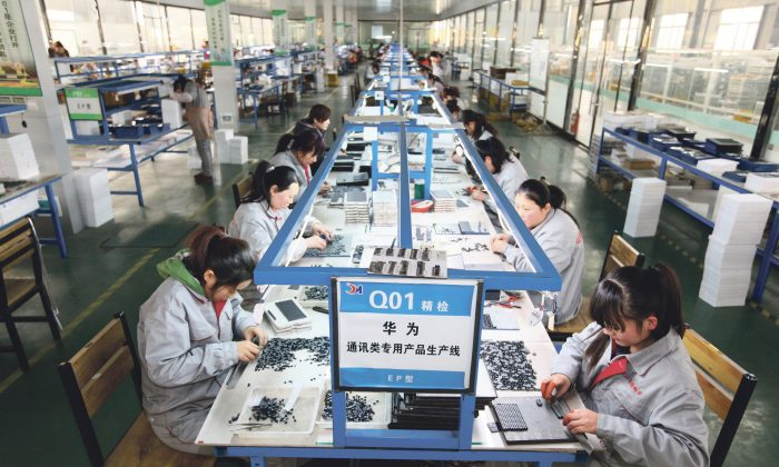 Workers sort parts at an electronics company in Tengzhou, in China's eastern Shandong province, on Feb 1, 2016. (STR/AFP/Getty Images)