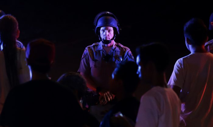 """A police officer blocks the on-ramp to a freeway during a protest Wednesday, Sept. 28, 2016, in El Cajon, Calif. Dozens of demonstrators on Wednesday protested the killing of Alfred Olango, a Ugandan refugee shot by a police officer after authorities said he pulled an object from a pocket, pointed it and assumed a """"shooting stance."""" (AP Photo/Gregory Bull)"""