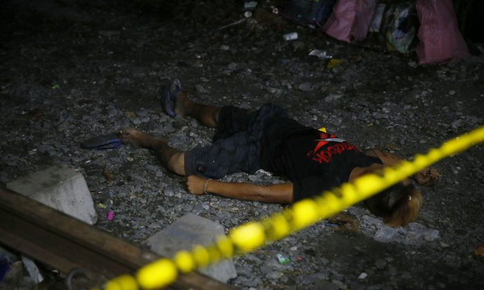 "FILE: The body of one of the three suspects killed in an alleged ""buy-bust"" operation by the authorities in the continuing ""War on Drugs"" campaign of Philippine President Rodrigo Duterte lies on the ground by the railroad tracks before dawn Friday, Sept. 30, 2016 in Caloocan city, north of Manila, Philippines. Duterte raised the rhetoric over his bloody anti-crime war to a new level Friday, comparing it to Hitler and the Holocaust and saying he would be ""happy to slaughter"" 3 million addicts. (AP Photo/Bullit Marquez)"