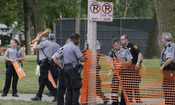 In this Monday, Aug. 15, 2016 file photo, police prepare to close a park in Milwaukee. A judge has ruled Sunday, Sept. 4, 2016, that a Milwaukee park at the center of a neighborhood where riots erupted after a police shooting last month can return to its normal hours for now.  (AP Photo/Jeffrey Phelps, File)