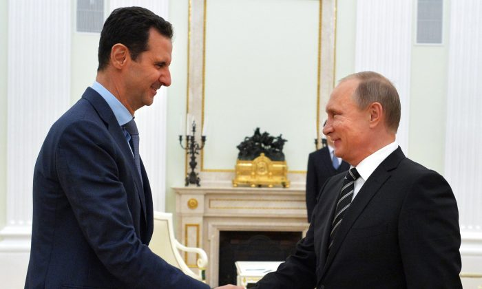 Russian President Vladimir Putin shakes hands with his Syrian counterpart Bashar al-Assad at the Kremlin in Moscow on Oct. 20, 2015. (ALEXEY DRUZHININ/AFP/Getty Images)