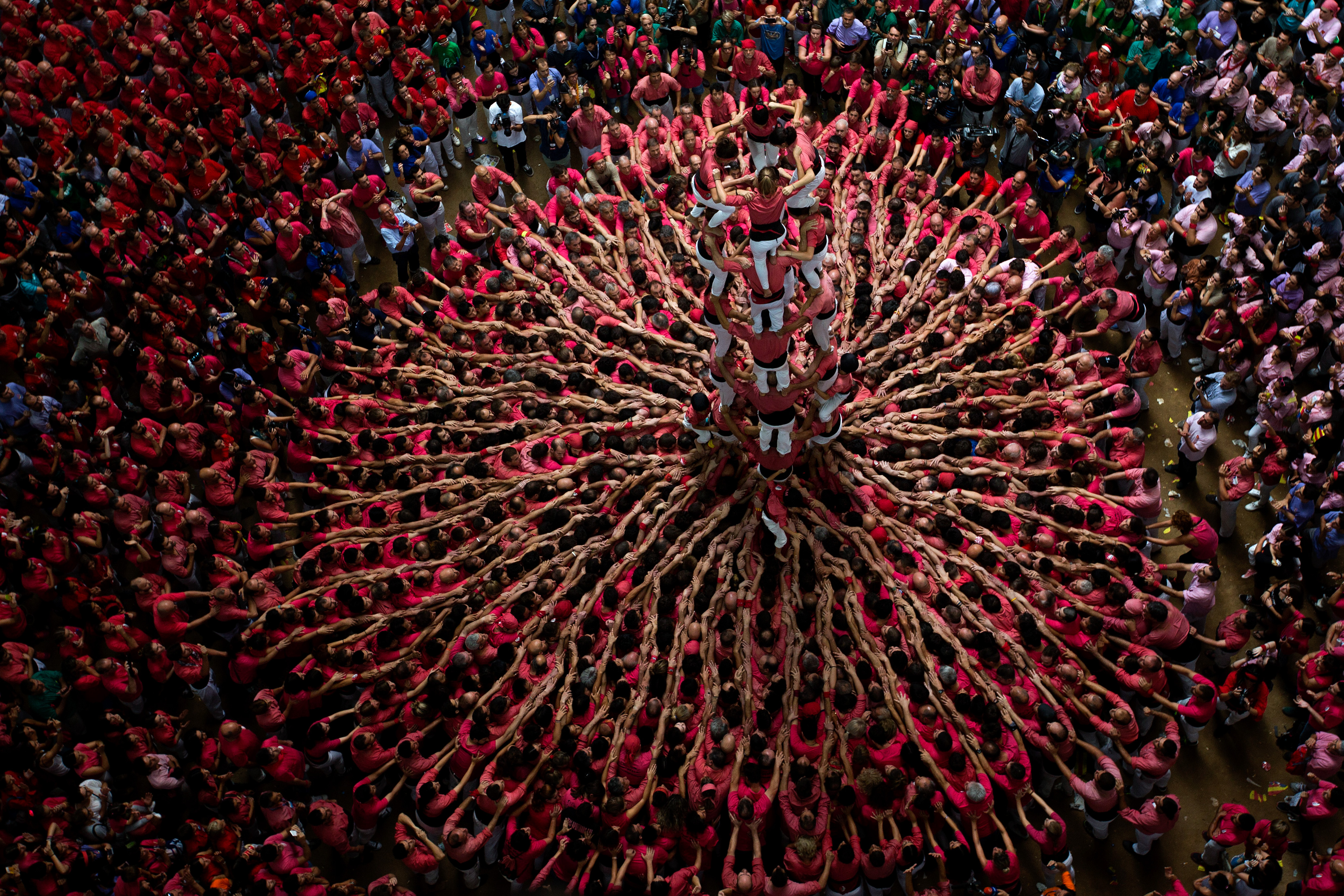 "Members of Vella de Xiquets de Valls try to complete their human tower during the Human Tower Competition in Tarragona, Spain, on Oct. 2. The tradition of building human towers, or Castells, dates back to the 18th century and takes place during festivals in Catalonia, where ""colles"", or teams, compete to build the tallest and most complicated towers. (AP Photo/Emilio Morenatti)"