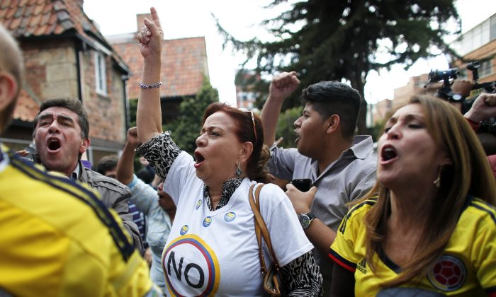 Opponents to the peace deal signed between the Colombian government and rebels of the Revolutionary Armed Forces of Colombia, FARC, celebrate the results of the referendum in Bogota, Colombia, on Oct. 2. (AP Photo/Ariana Cubillos)