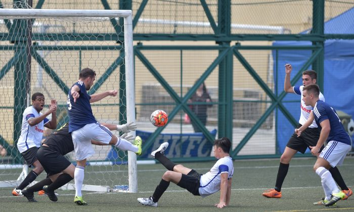 Goalmouth action between Club Wanderers (in blue top) and French Kiss in the Yau Yee League division 1 match at Sports Road on Sunday Oct 2, 2016. (Bill Cox/Epoch Times)