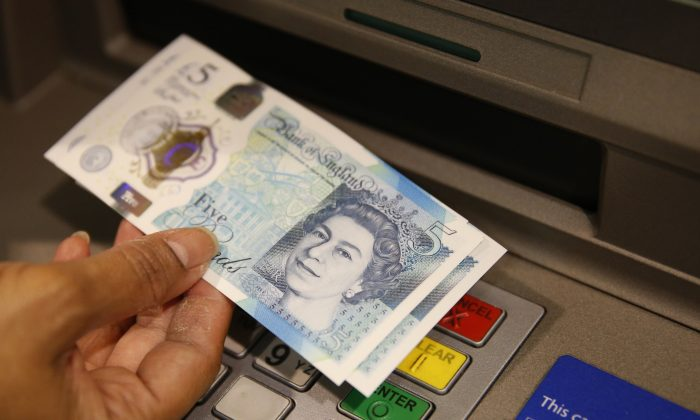 A member of staff at a branch of Halifax bank, in London, displays a new British 5 pound sterling note on Sept. 13, 2016.  (AP Photo/Alastair Grant, File)