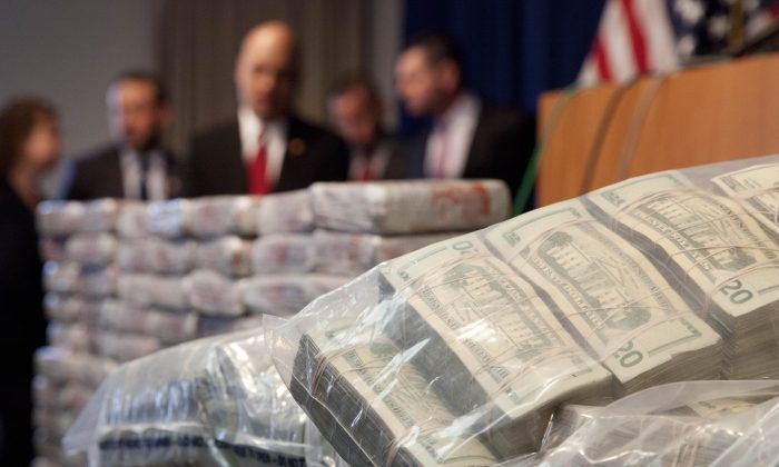 Sacks of money (R) worth $2 million and 154 pounds of heroin (L) worth at least $50 million are displayed at a Drug Enforcement Administration news conference in New York on May 19, 2015. (Mark Lennihan/AP Photo)