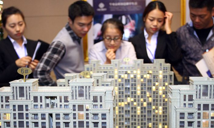 Customers and real estate agents look at several building models at a real estate exhibition in Jiashan, Zhejiang Province on Oct. 19, 2012. (AFP/AFP/Getty Images)