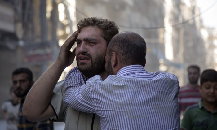 Syrians react as the bodies of children are pulled from the rubble of a budling following government forces airstrikes in the rebel-held neighborhood of Al-Shaar in Aleppo on Sept. 27, 2016. (Karam al-Masri/AFP/Getty Images)