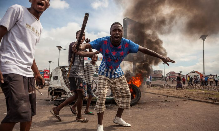 Demonstrators gather in front of a burning car during an opposition rally in Kinshasa on Sept. 19, 2016. Police fired tear gas at scores of opposition supporters rallying in Kinshasa to demand that DR Congo's long-serving President Joseph Kabila step down this yea (AFP / EDUARDO SOTERAS/Getty Images)