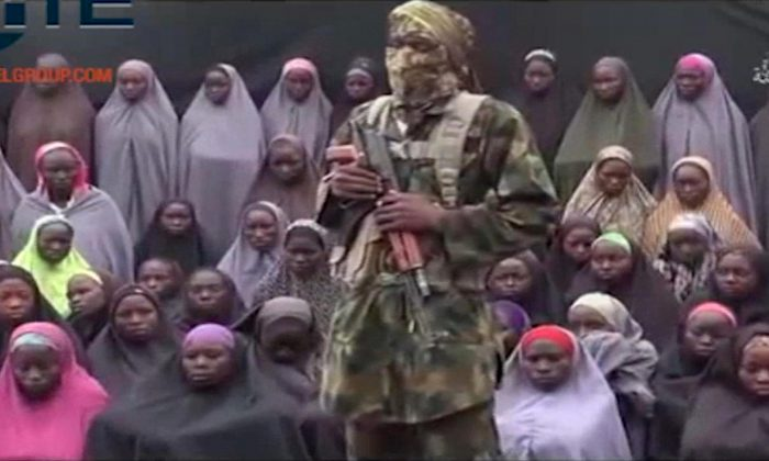 An alleged Boko Haram soldier standing in front of a group of girls alleged to be some of the 276 abducted Chibok schoolgirls held since April 2014, in an unknown location. (Militant video/Site Institute via AP)