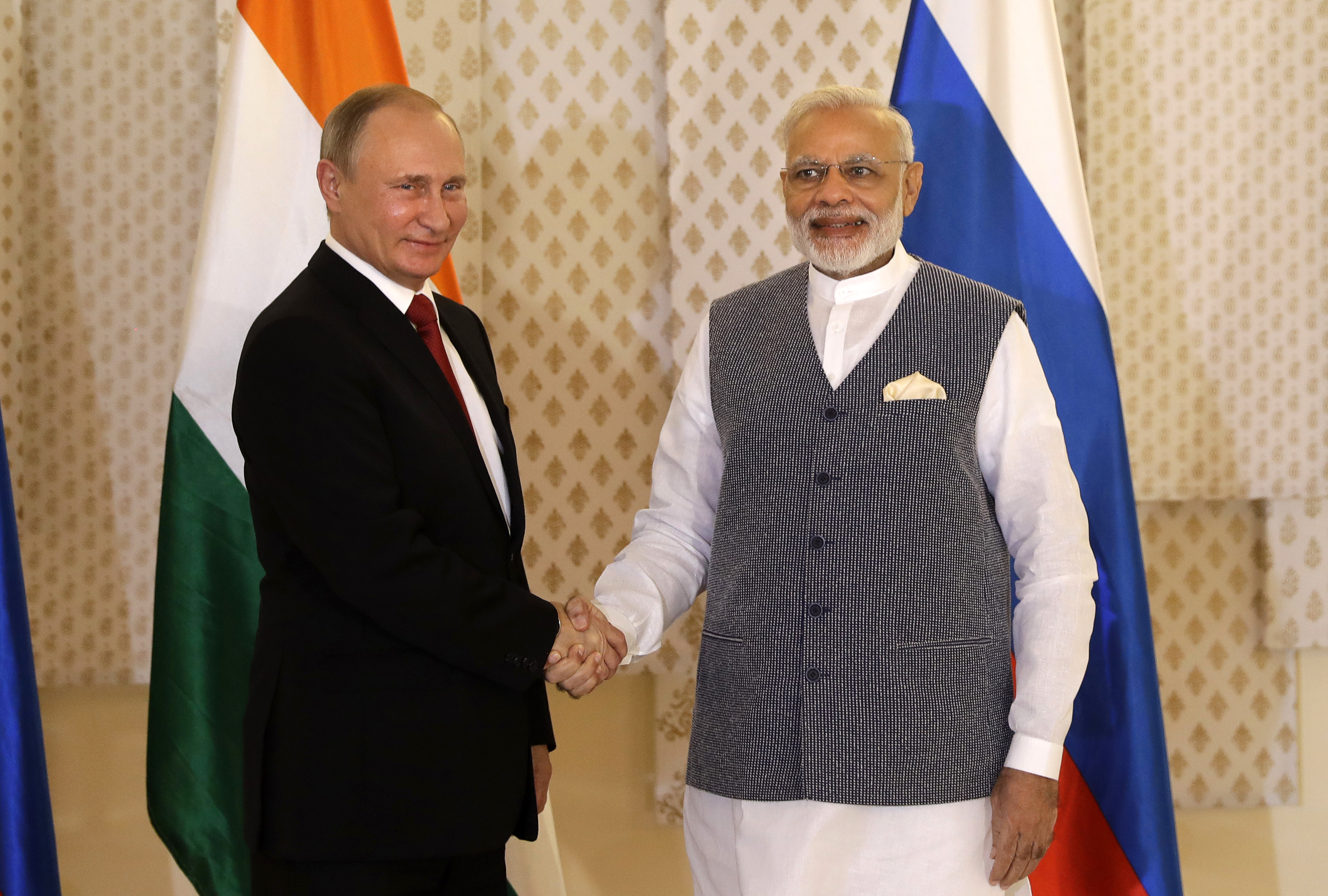 Indian Prime Minister Narendra Modi (R) shakes hand with Russian President Vladimir Putin prior to their annual bilateral meeting, on the sidelines of the BRICS summit, where they are expected to discuss Syria and Afghanistan, in Goa, India, on Oct. 15, 2016. (AP Photo/Manish Swarup)