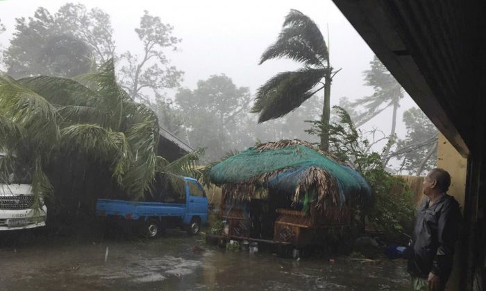 A man takes cover as strong winds and rain topple trees while Typhoon Haima lashes Narvacan, Ilocos Sur, northern Philippines on Thursday Oct. 20, 2016. Super Typhoon Haima slammed into the northeastern Philippine coast late Wednesday with ferocious winds and rain that rekindled fears and memories from the catastrophe wrought by Typhoon Haiyan in 2013. (AP Photo/Bullit Marquez)
