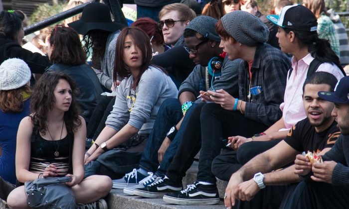 Teens smoke on the steps of Union Square park in New York on March 8, 2012. (Benjamin Chasteen/Epoch Times)